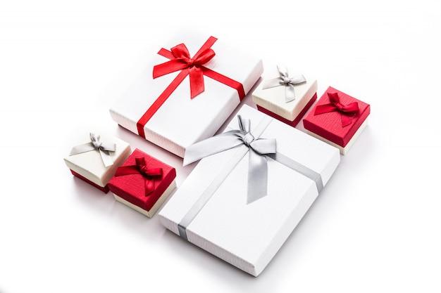 Белые и красные подарочные коробки изолированные на белизне.