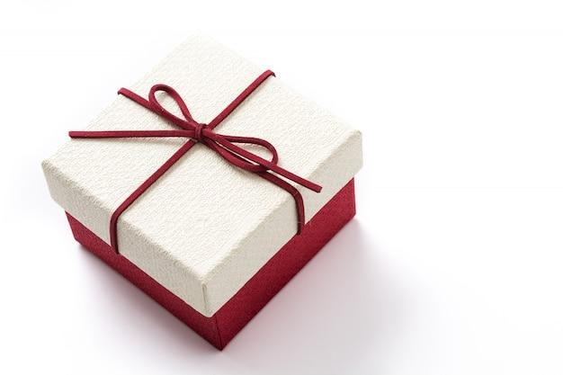 Белая и красная подарочная коробка изолированная на белизне.