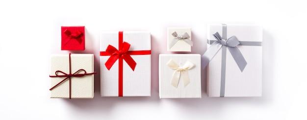Белые и красные подарочные коробки изолированные на белизне. панорамный вид