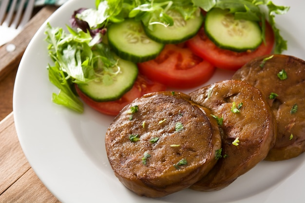 Сейтан с овощами на деревянном столе. поддельное мясо.