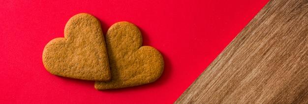 ハート形の赤い背景のクッキー。パノラマビュー。バレンタインデーと母の日のコンセプト。
