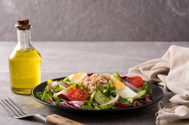 Салат с тунцом, яйцом и овощами на черной тарелке и сером фоне