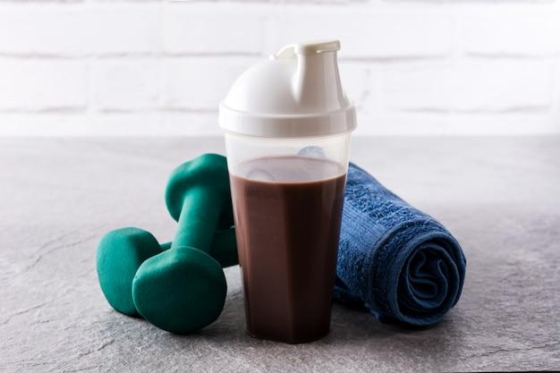 Шоколадный протеиновый коктейль и гантели на сером камне