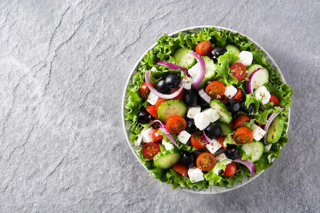 Свежий греческий салат в тарелке с черными оливками, помидорами, сыром фета, огурцом и луком на сером фоне вид сверху копией пространства