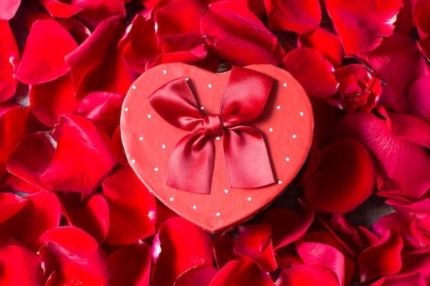 Подарочная коробка в форме сердца на фоне лепестков