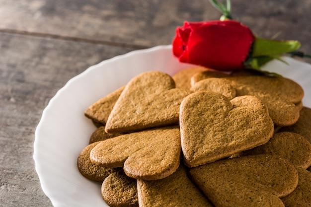 ハート型のクッキーと赤いバラ