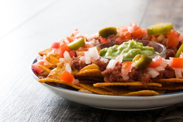 メキシコのナチョス、牛肉、ワカモレ、チーズソース、ピーマン、トマト、木製テーブルの上の皿にタマネギ