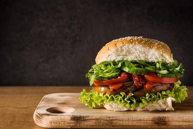 Вегетарианский бургер с сейтаном и овощами на деревянном столе