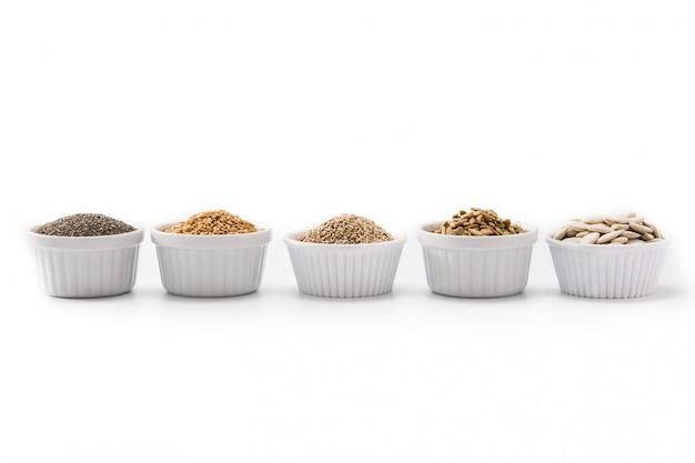 Ассортимент различных семян в миске на белом фоне семена тыквы, льна, чиа, подсолнечника и кунжута