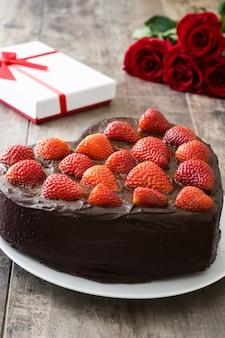 ハート形の木製の背景にバレンタインの日や母の日ケーキ