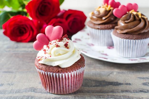 木製のテーブルに砂糖の心とバラの表面で飾られたバレンタインカップケーキ