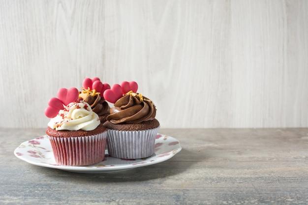 木製テーブルコピースペースに砂糖の心で飾られたバレンタインカップケーキ