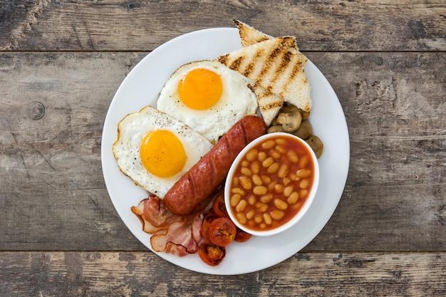 Традиционный полный английский завтрак с жареными яйцами, сосисками, бобами, грибами, жареными помидорами и беконом на деревянной поверхности
