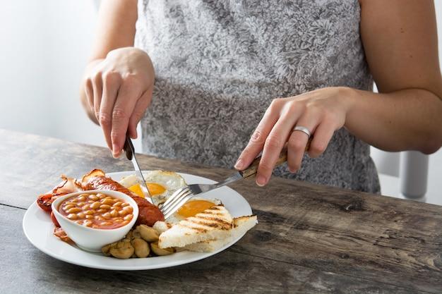Женщина ест традиционный английский завтрак с яичницей, сосисками, фасолью, грибами, жареными помидорами, беконом на деревянном столе