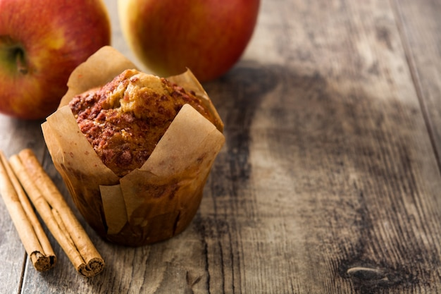 リンゴと木製のテーブルにシナモンのマフィン。