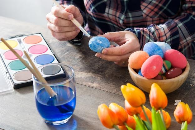 Женщина красит пасхальные яйца на деревянный стол