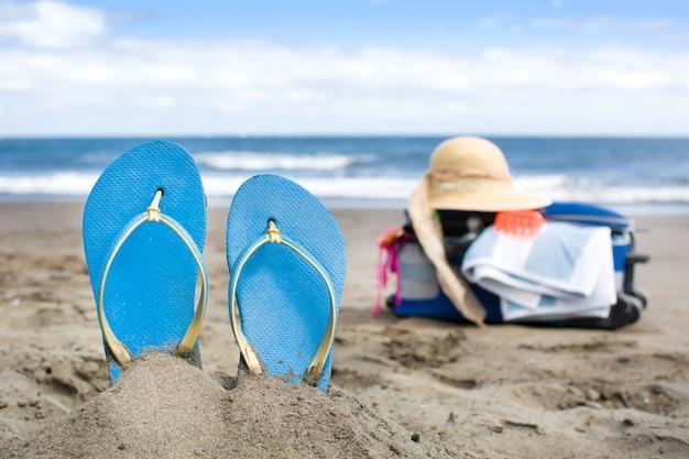 Летняя обувь на песке пляжа с чемоданом путешествия