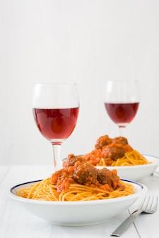 Итальянские спагетти с соусом и фрикадельками на белом деревянном столе