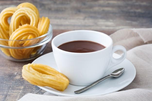 Горячий шоколад с чурросом на деревянном столе испанский завтрак