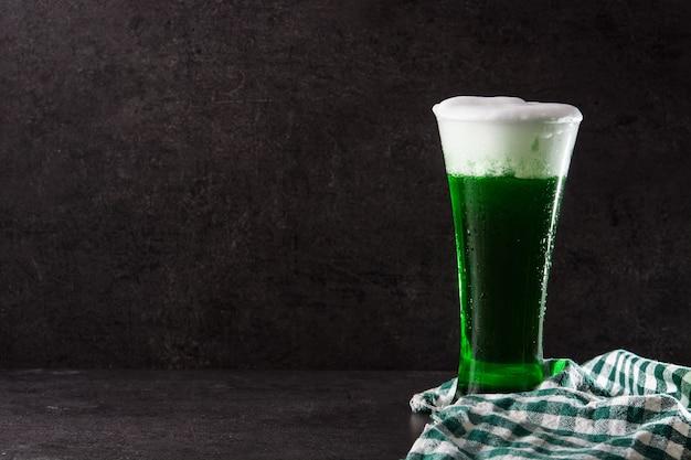 黒い背景に伝統的な聖パトリックの日の緑ビールコピースペース