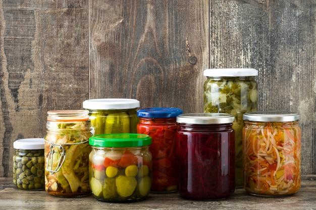 Заквашенные сохраненные овощи в опарнике на деревянном столе.