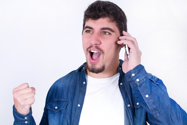分離された携帯電話で話している幸せな若い男