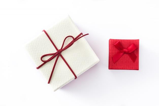 Белые и красные подарочные коробки изолированные на белизне. вид сверху