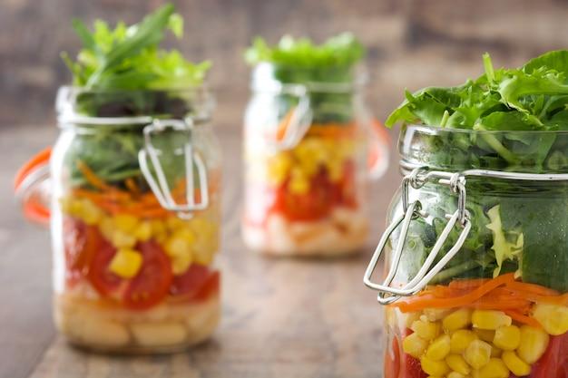白豆、トマト、タマネギ、トウモロコシ、木製のテーブルにレタスと石工の瓶にヘルシーなサラダ