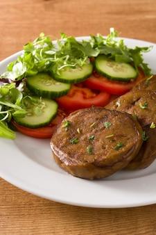 Сейтан с овощами на деревянном столе поддельное мясо крупным планом