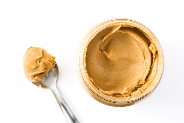 Сливочное арахисовое масло и ложка, изолированные на белой поверхности вид сверху