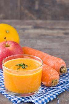 オレンジ、リンゴ、ニンジンの木製テーブルのスムージー