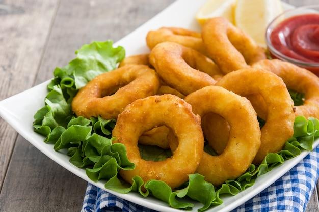 Жареные кольца кальмаров с листьями салата и кетчупом на деревянной поверхности