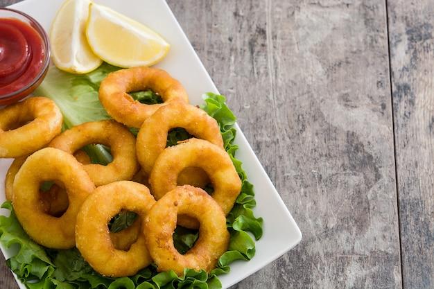 Жареные кольца кальмаров с листьями салата и кетчупом на деревянной поверхности копией пространства