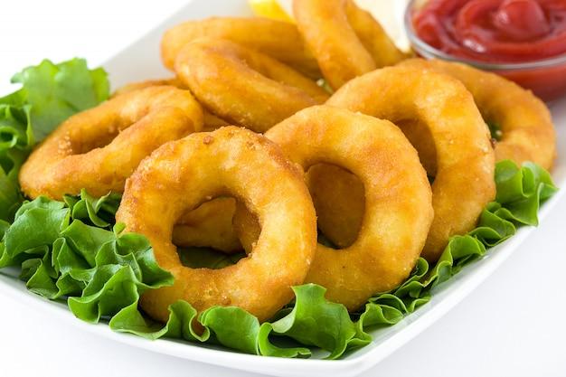 Жареные кольца кальмаров с листьями салата и кетчупом, изолированные на белой поверхности
