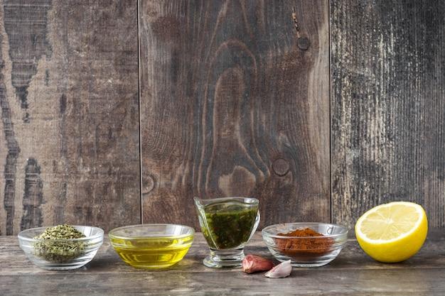 Зеленый соус чимичурри и ингредиенты на деревянный стол