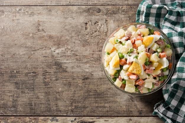 Традиционный русский салат и ингредиенты, салат оливье на деревянный стол.