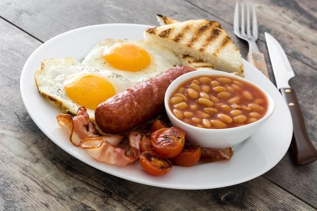 Традиционный полный английский завтрак с яичницей, сосисками, фасолью, грибами, жареными помидорами и беконом на деревянной поверхности.