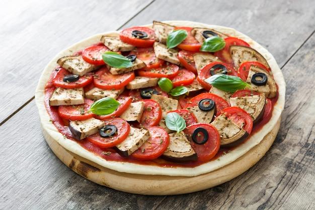 木製のテーブルにナス、トマト、ブラックオリーブ、オレガノ、バジルのベジタリアンピザを表示