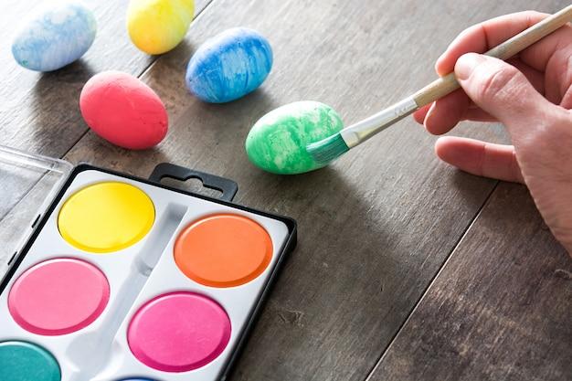 Роспись красочных пасхальных яиц на деревянном столе