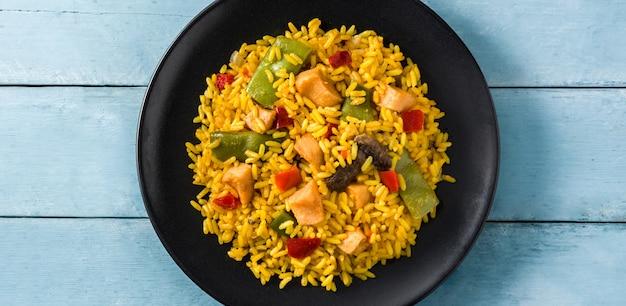 青い木製テーブルパノラマビューに黒い皿に野菜と鶏肉のチャーハン