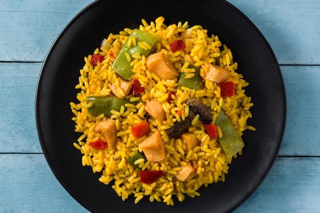 青い木製テーブルの上の黒い皿に野菜と鶏肉のチャーハンをクローズアップ