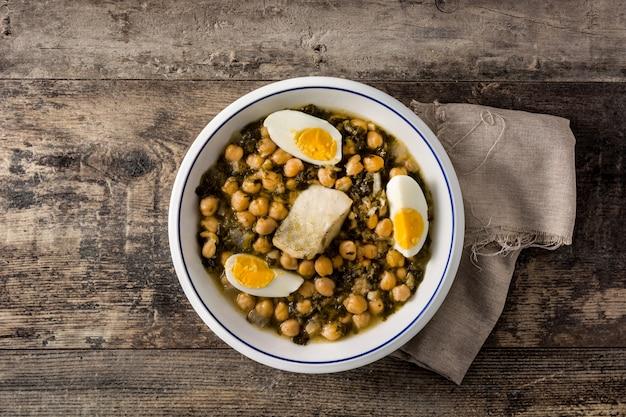 ひよこ豆のシチューとほうれん草とタラまたはポタヘデビジリアトップビューイースター休暇の典型的なスペイン料理。