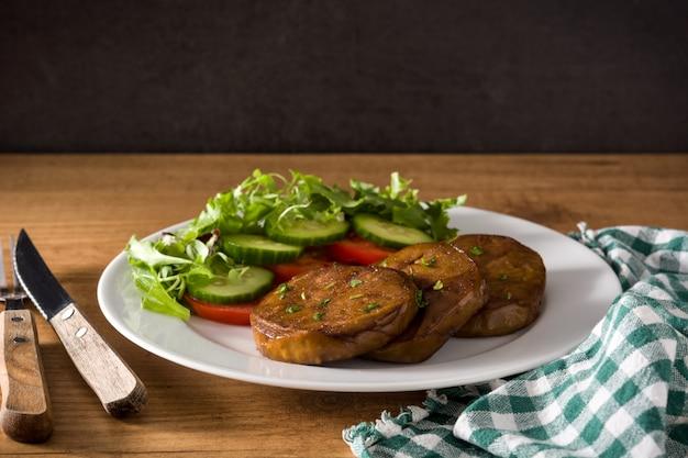 Сейтан с овощами на деревянном столе поддельное мясо