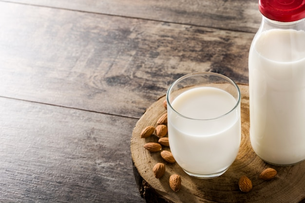 Органическое миндальное молоко в стекле и бутылке на деревянном столе. копировать пространство