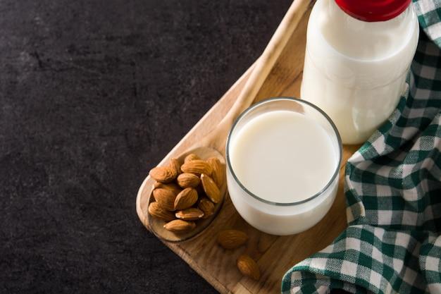 Миндальное молоко в стакан и бутылка на черном. копировать пространство