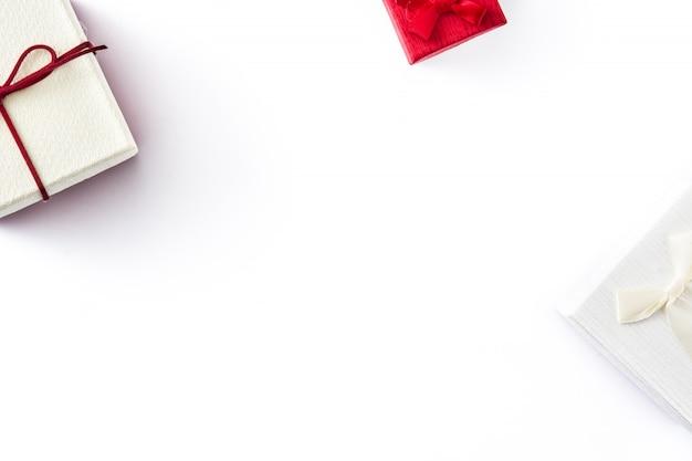 Белая и красная подарочная коробка изолированная на белизне. вид сверху.