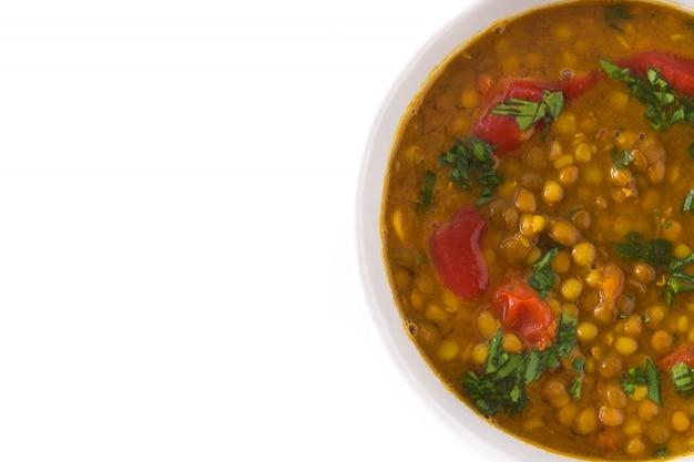 白で隔離されるボウルにインドのレンズ豆のスープダル(ダル)。