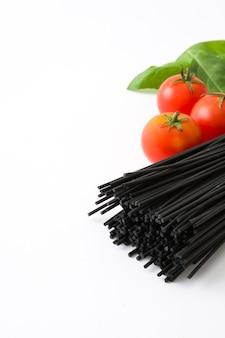 トマトとバジルを白で隔離される黒スパゲッティ