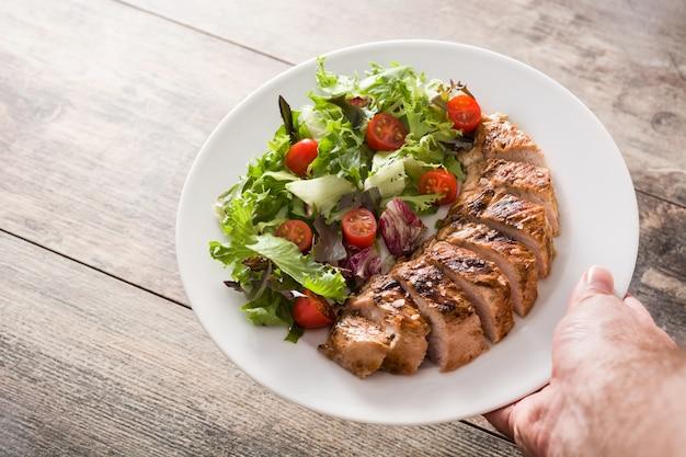 木製テーブルの上の皿に野菜と鶏の胸肉のグリル。