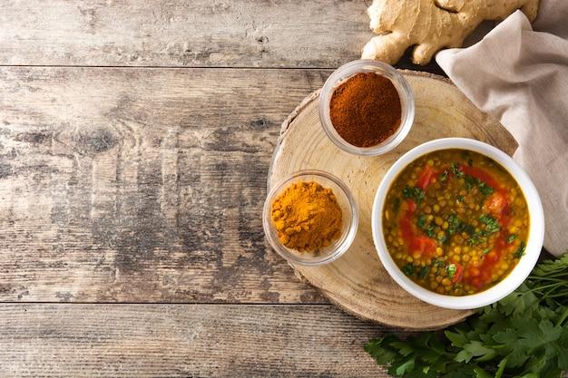 木製のテーブルの上にボウルにインドのレンズ豆のスープダル(ダル)。上面図。コピースペース